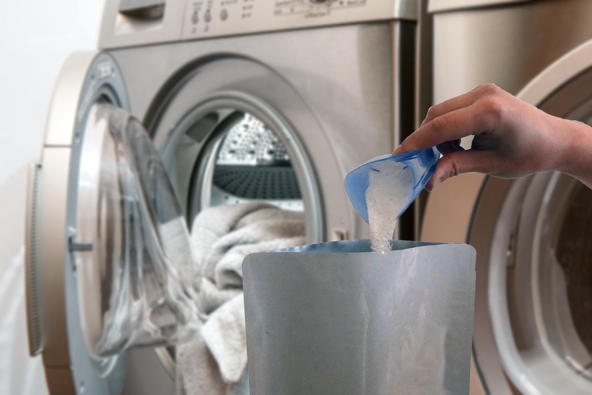 Waschmittelverpackung mit Waschmaschine im Hintergrund